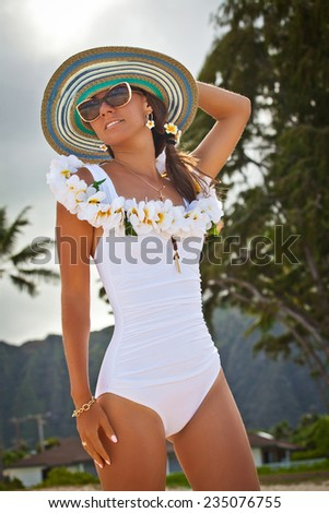 Beautiful smiling woman in white bikini and straw hat posing on the beach with welcoming Lei on the hawaiian island Oahu Island. Summer luxury vacation. - stock photo