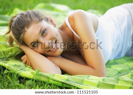 Beautiful smiling woman laying on the grass - stock photo