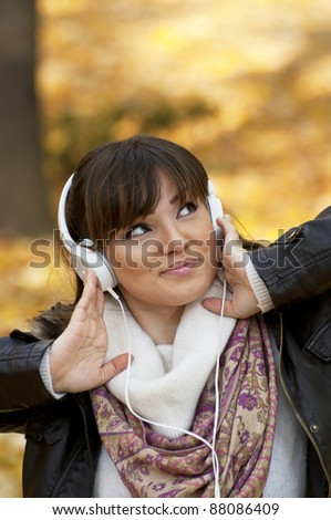 Beautiful smiling woman listening to music and dancing - stock photo