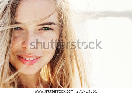 Beautiful Smiling Woman Looking at Camera with Hair Blowing in the Wind. in Sunlight. Warm Color Toned - stock photo