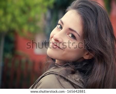 Beautiful smiling woman looking happy outdoors background - stock photo