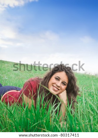Beautiful smiling woman lying on a green meadow - stock photo
