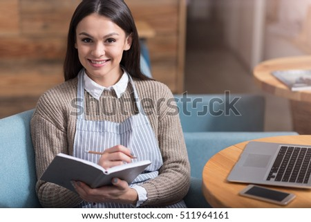 Beautiful smiling woman making notes and sitting on an armchair