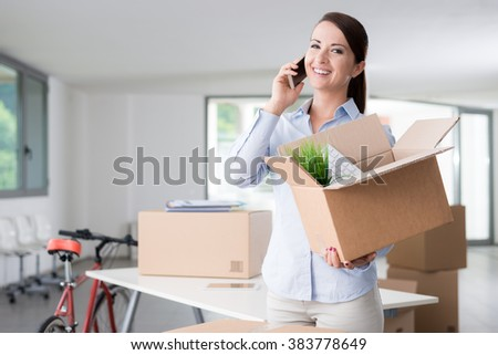 Beautiful smiling woman moving in a new office, talking on the phone and holding an open cardboard box - stock photo