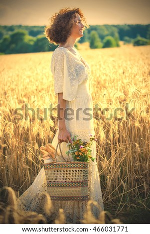 Beautiful smiling Woman Outdoors with wicker bag with natural meal and flowers. Pretty female Model in white dress goes on the summer Field, Sun Light. Glow Sun. instagram image filter retro style