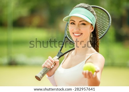 Beautiful smiling woman playing tennis outdoors in the morning. - stock photo