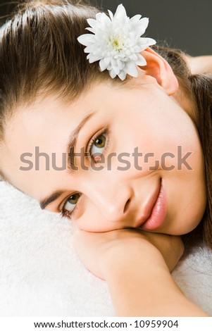 Beautiful smiling woman putting head on her hand - stock photo