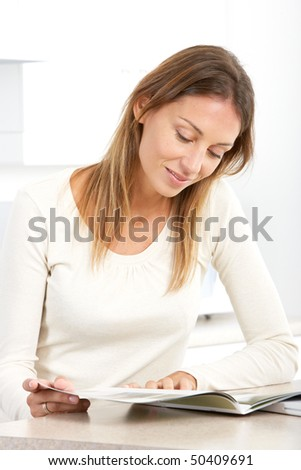 Beautiful smiling woman reading newspaper  in kitchen