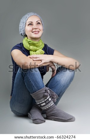 Beautiful smiling woman sitting comfortably on gray background - stock photo