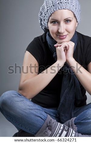 Beautiful smiling woman sitting comfortably over grey background