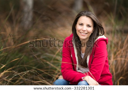 Beautiful smiling woman sitting in brown grass - stock photo