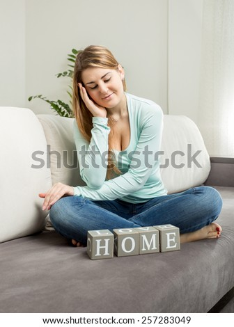 "Beautiful smiling woman sitting on sofa and looking on word ""home""  - stock photo"