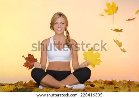 beautiful smiling woman sitting practice yoga under leaves - stock photo
