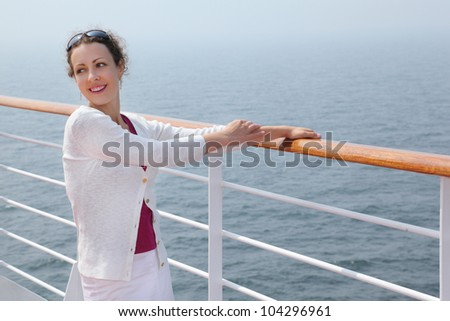 Beautiful smiling woman stands on board of large ship and clings to railing - stock photo