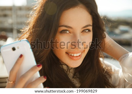 beautiful, smiling woman take a picture of herself with a smartphone. selfie, outdoors shot, horizontal - stock photo