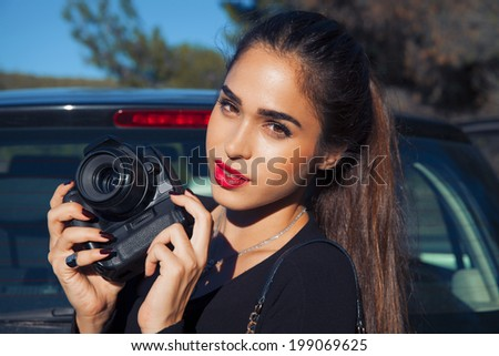 Beautiful, smiling woman take a picture with digital camera. outdoors shot, horizontal - stock photo