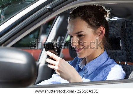 Beautiful smiling woman texting on mobile phone at car - stock photo