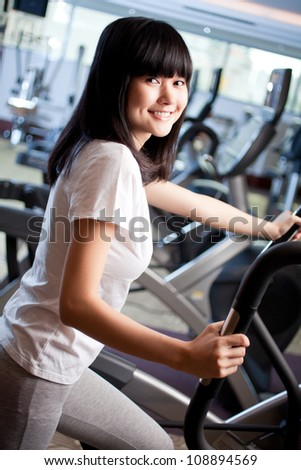 Beautiful smiling woman training in gym - stock photo