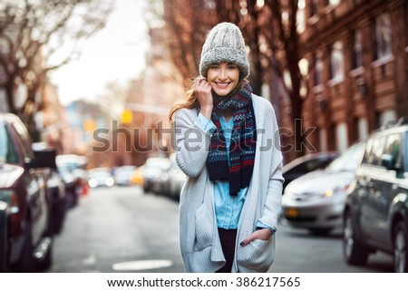 Beautiful smiling woman walking on city street wearing casual style clothes - stock photo