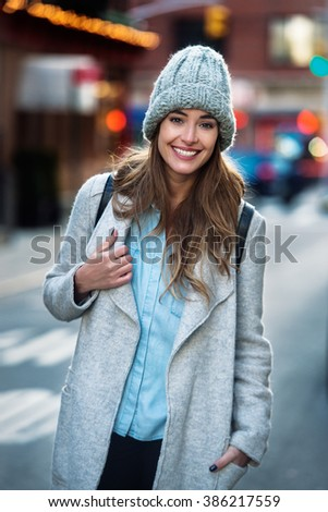 Beautiful smiling woman walking on the New York City street wearing casual style clothes - stock photo