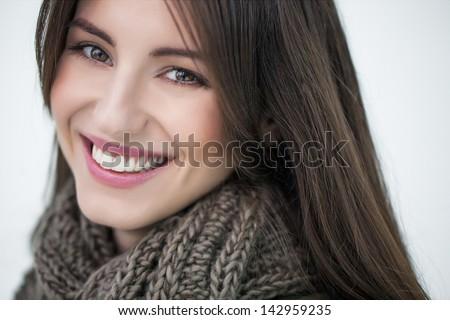 Beautiful smiling woman wearing a warm woolen scarf. - stock photo