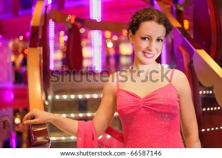 beautiful smiling woman wearing evening dress in illuminated hall.