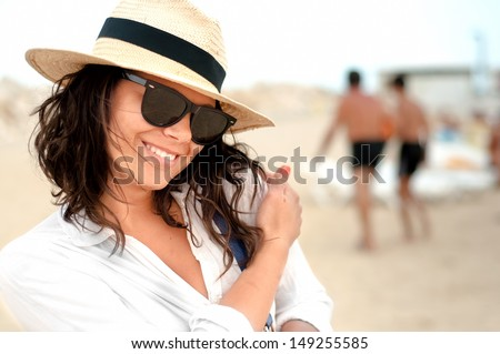 Beautiful, smiling woman wearing hat and glasses on private beach at resort - stock photo