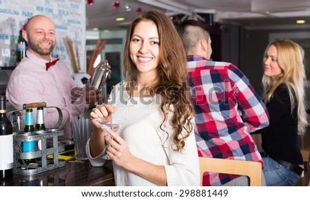 Beautiful smiling woman with a cocktail at a party in a bar. With a bartender and a couple on the background - stock photo