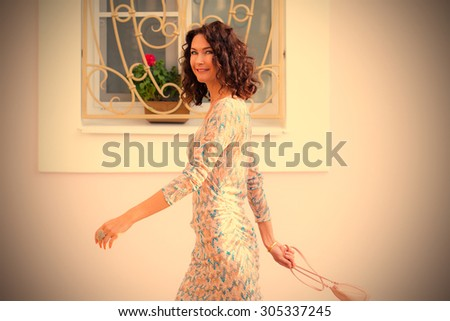 Beautiful smiling woman with a small handbag goes misses the bright wall of the house with barred window. instagram image filter retro style - stock photo