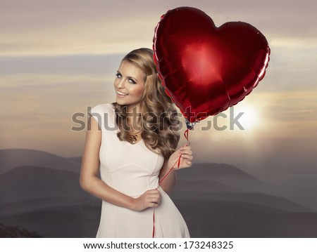 Beautiful smiling woman with balloon on background of mountains  - stock photo