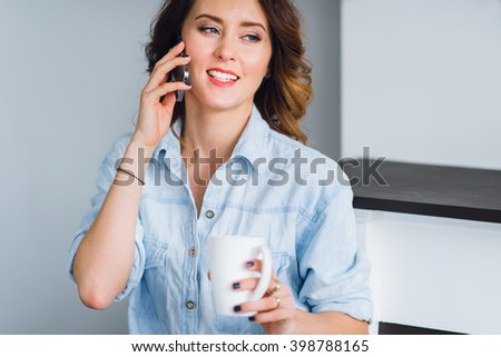 Beautiful smiling woman with coffee cup talking on a cell phone at home. - stock photo
