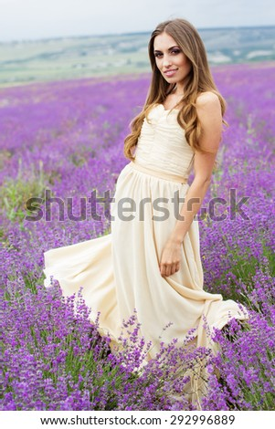 Beautiful smiling woman with flying hair and dress holding bouquet at field of purple lavender flowers  - stock photo