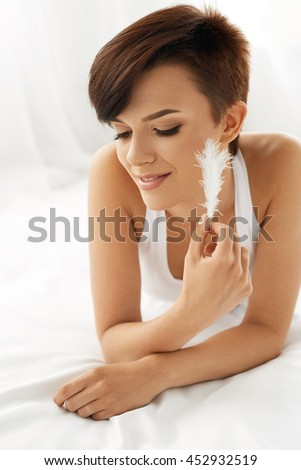 Beautiful Smiling Woman With Fresh Face Touching Her Soft Skin With White Feather Lying On Bed. Closeup Portrait Of Healthy Happy Girl With Natural Makeup Relaxing Indoors. Beauty, Skin Care Concept