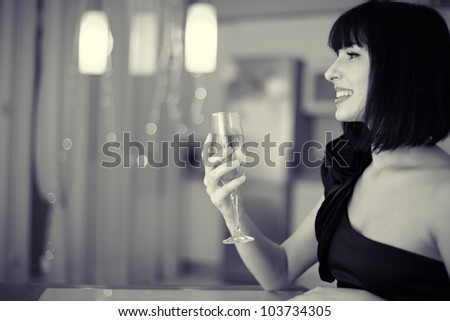 beautiful smiling woman with glass of champagne at restaurant - stock photo