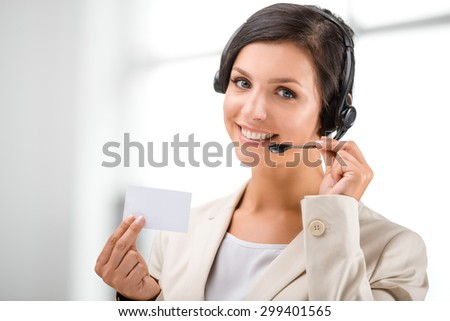 Beautiful smiling woman with headphones looking at camera and holding blank visit card at call center