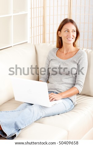 Beautiful smiling woman with laptop  at home