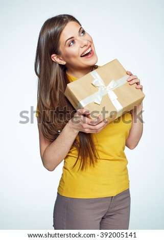 Beautiful smiling woman with long hair holding gift box. White background isolated studio portrait.