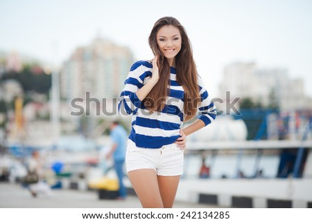 Beautiful smiling woman with long hair. In city. - stock photo