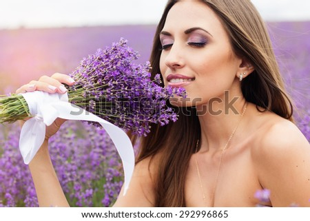 Beautiful smiling woman with nice makeup with bouquet at field of purple lavender flowers  - stock photo