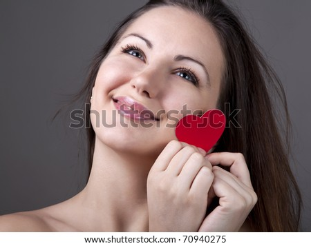 Beautiful smiling woman with red heart - stock photo