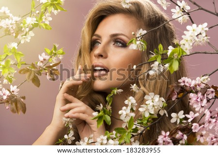 Beautiful smiling  woman with spring flowers and big hair  - stock photo