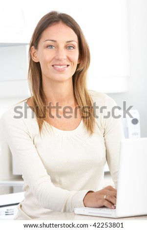 Beautiful smiling woman working with laptop in kitchen