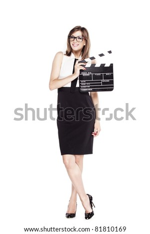 Beautiful smiling womanl, with glasses, dressed in a black and white dress with a tie and black high heel pumps, holding a film clapper board, on a white background.
