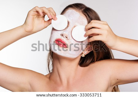 Beautiful smiling women with white clay facial mask on her face is holding cotton pads on hands near eyes - stock photo