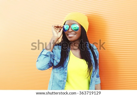 Beautiful smiling young african woman wearing a sunglasses over orange background - stock photo