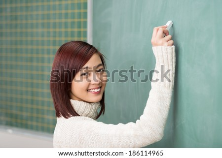 Beautiful smiling young Asian student writing on a blank blackboard with a piece of chalk turning to give the camera a lovely smile - stock photo