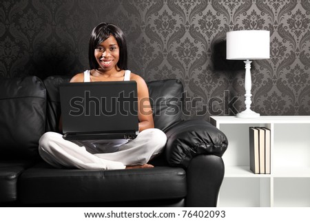 Beautiful smiling young black woman sitting cross legged on leather sofa at home, surfing the internet with her laptop computer. - stock photo