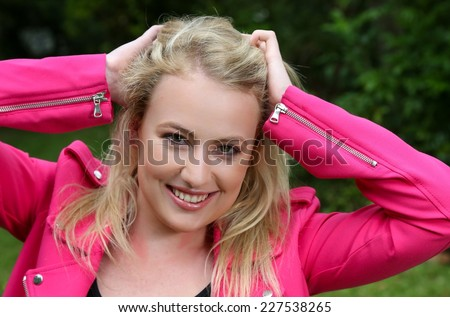 Beautiful smiling young blond woman in a pink jacket - stock photo