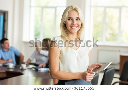 Beautiful smiling young blonde woman with tablet computer in the business office.