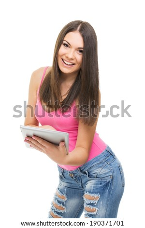 Beautiful smiling young Caucasian brunette woman with digital tablet computer. Cute happy teenage girl laughing using tablet wearing pink shirt and ripped jeans isolated on white background. - stock photo